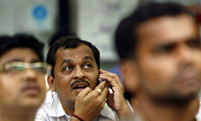 A stock trader talks on his mobile phone.