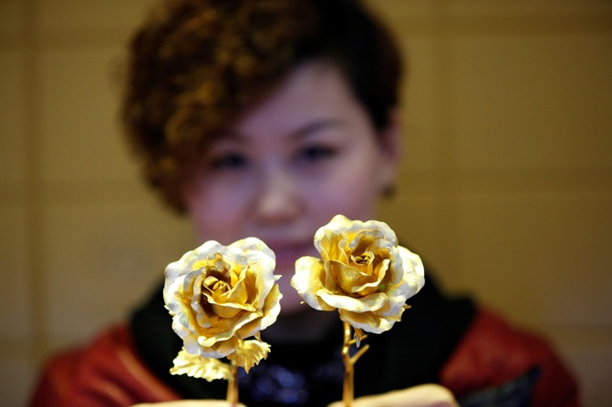 A woman holds golden roses on Valentines' Day at a gold store.