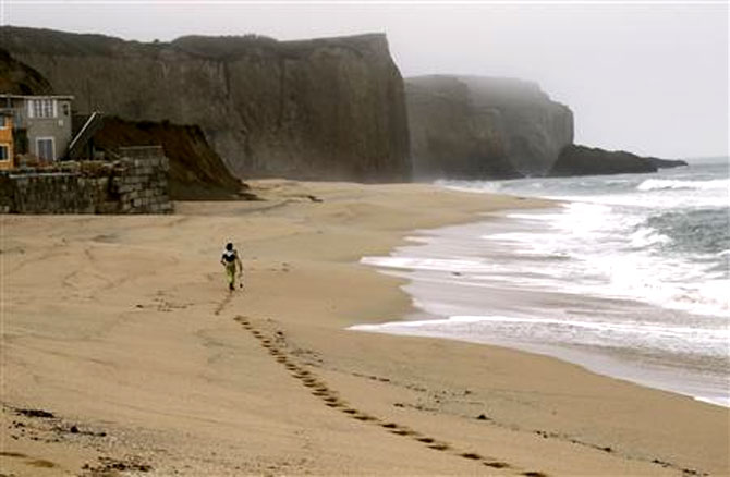 A surfer heads to a surfing spot at Martin's Beach, a popular surfing and fishing spot, in Half Moon Bay, California.