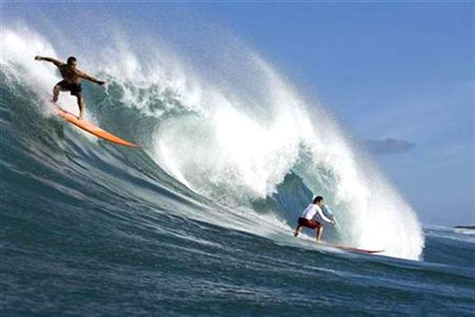 Surfers catch a wave.