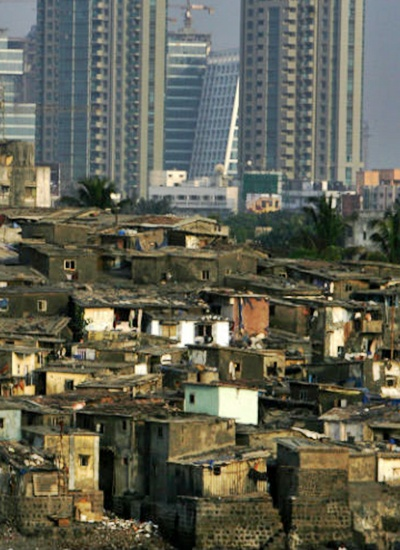 High rise buildings are seen behind a slum in Mumbai.