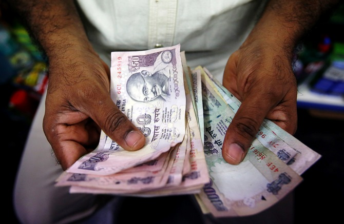 A private money trader counts Indian Rupee currency notes at a shop in Mumbai.