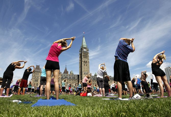 People take part in a free weekly yoga class on the front lawn of Parliament Hill in Ottawa.