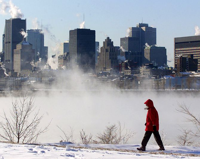 Ice fog rises from the St. Lawrence River as woman walks along the river bank in Montreal.