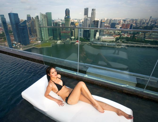 A model lies on a bed in the infinity pool of the Skypark that tops the Marina Bay Sands hotel towers in Singapore.