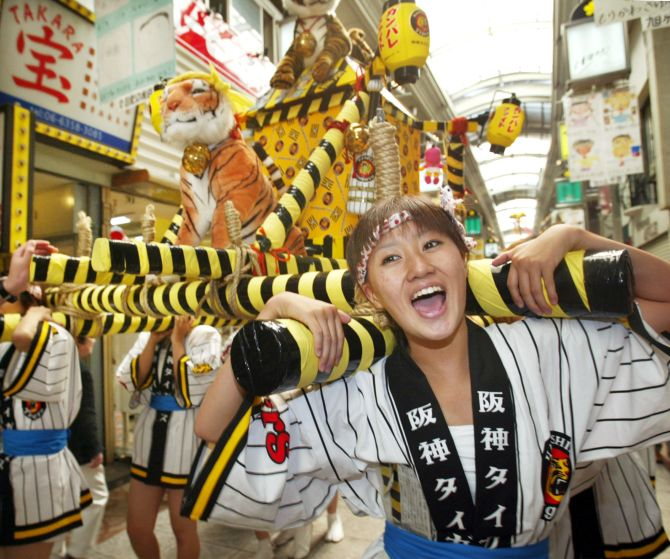 Japanese mikoshi girls shout as they lift a mikoshi, or portable shrine,  in Osaka.