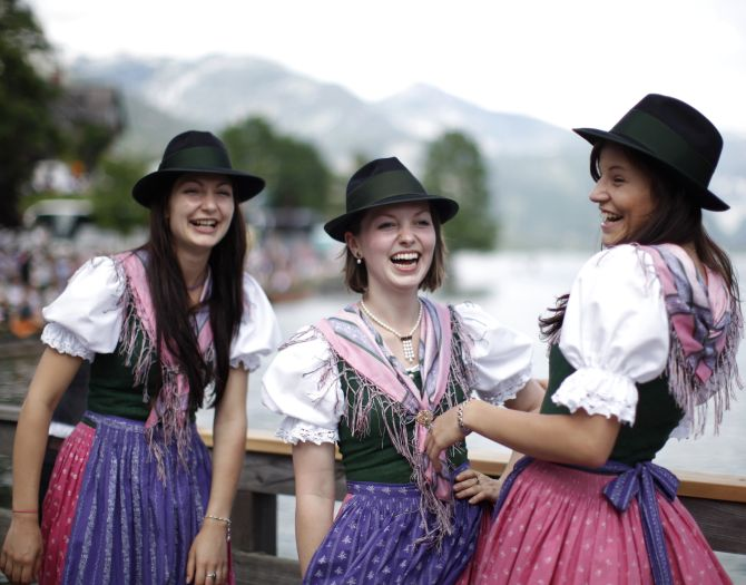 Women in traditional Dirndl dresses watch a boat parade during Narzissenfest (Daffodil Festival) at Grundlsee lake.