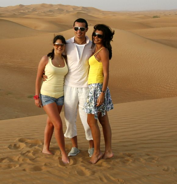 Tourists pose for pictures in the Dubai desert.