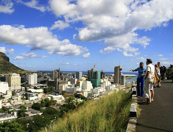 A tour guide stands with a group of tourists at a viewpoint overlooking Port Louis.