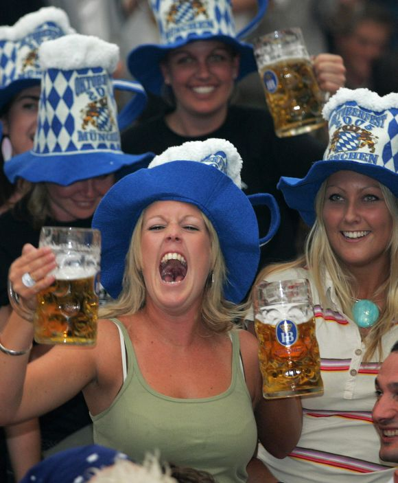 A woman shouts out as she drinks beer during the opening day of Munich's famous Oktoberfest.