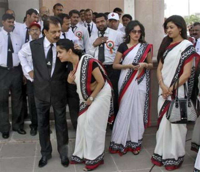 Subrata Roy (front, L) speaks with an employee.