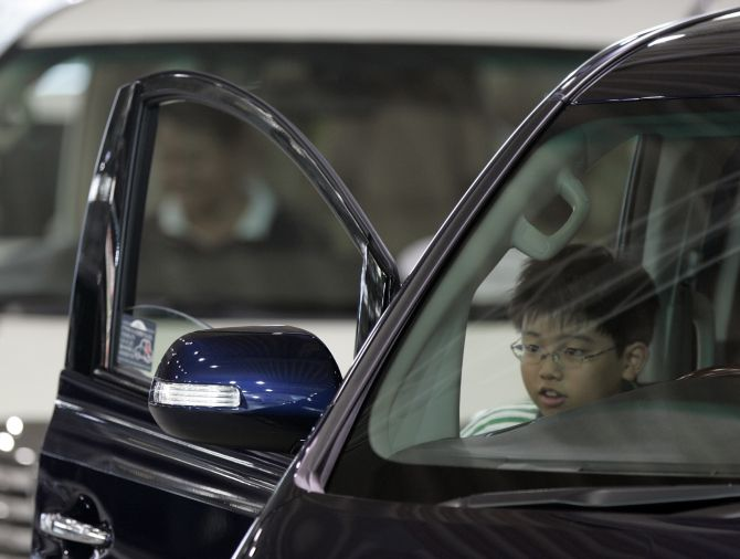 A boy takes a seat inside a car at a Toyota Motor Corp showroom.
