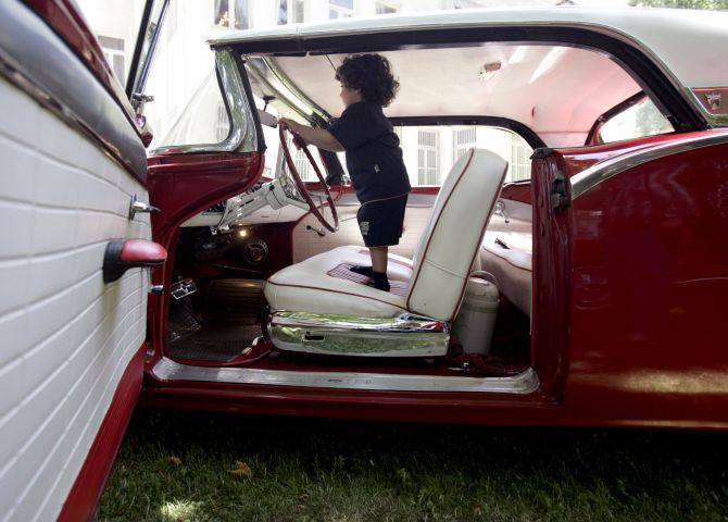 A child plays at the wheel of a 1957 Ford car.
