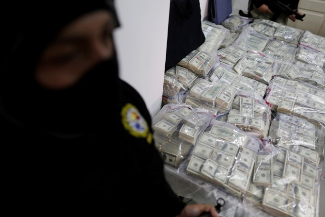 Panama police stand guard over $7 million confiscated by the police during a news conference in Panama City January 13, 2014.