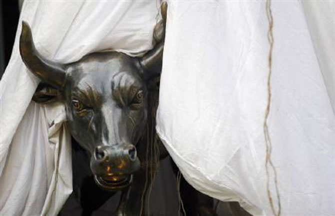 A bronze replica of a bull is seen at the gates of the Bombay Stock Exchange building.