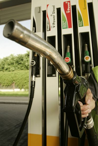 A worker holds a petrol pump nozzle.