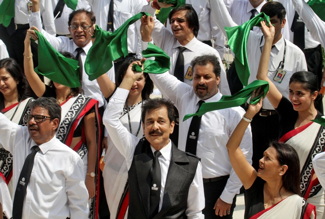 Sahara Group Chairman Subrata Roy (C, bottom) waves a green cloth together with his employees after singing India's national anthem in the northern Indian city of Lucknow May 6, 2013.