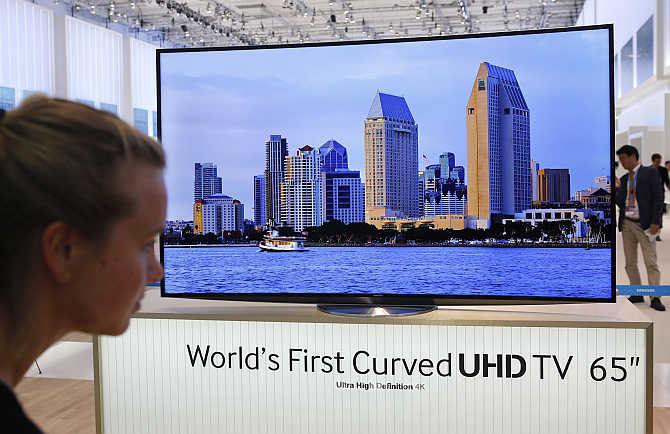 A women looks at the world's first curved UHD TV 55 4K screen at the booth of Samsung at the IFA consumer electronics fair in Berlin, Germany.