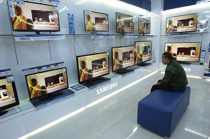 A visitor looks at television screens in a shopping centre in Makassar in South Sulawesi province, Indonesia.