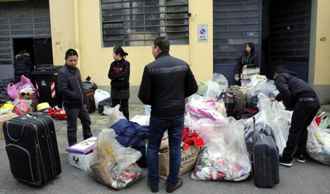 Chinese immigrants pack their belongings after police officers finished checking the Shen Wu textile factory in Prato.