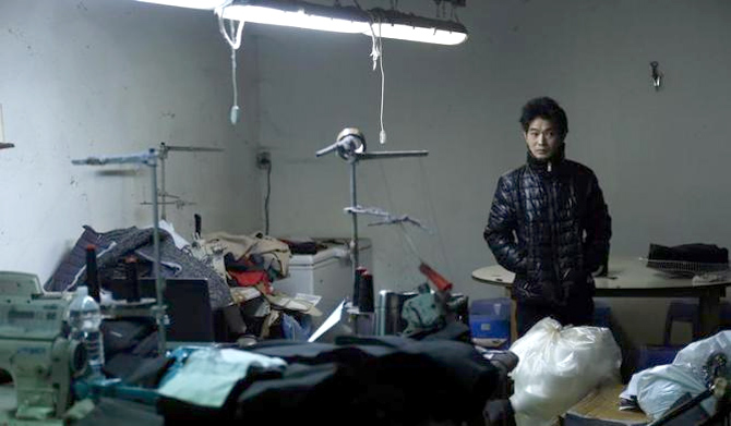 A Chinese immigrant looks on as police officers conduct a check at a textile factory in Prato.