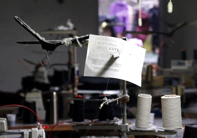 A paper that reads Equipment confiscated is seen on an industrial sewing machine as police officers conduct a check at the Shen Wu textile factory in Prato.