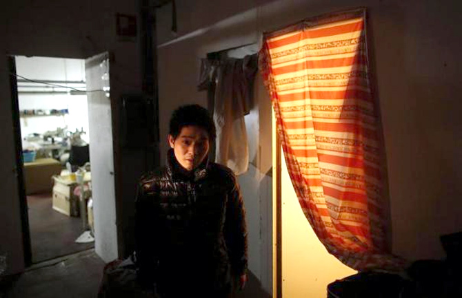 A Chinese immigrant stands near his room as police officers conduct a check at the Shen Wu textile factory in Prato.