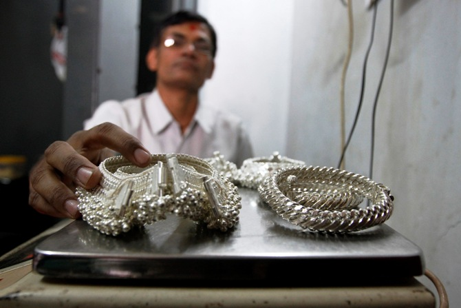 A silver trader weighs his silver ornaments inside his shop in Ahmedabad.