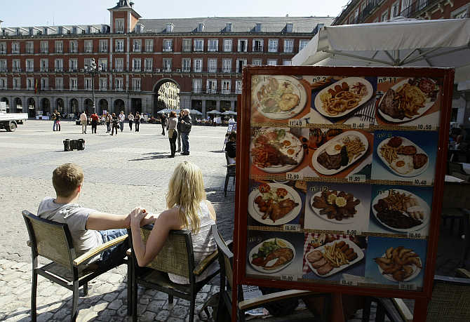 People sit in a restaurant in Madrid's central Plaza Mayor, Spain.