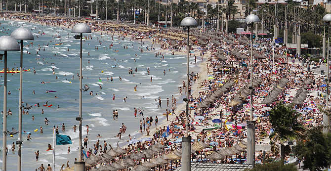 Tourists crowd Palma de Mallorca's Arenal beach in the Spanish Balearic island of Mallorca.