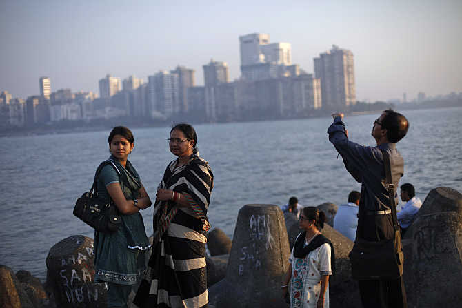 People walk at a seafront promenade in the evening at the Nariman Point financial area in south Mumbai.