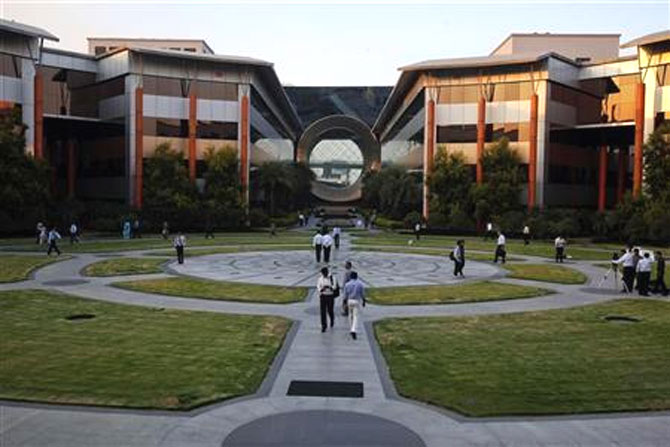 Employees walk in front of a building dubbed the ''washing machine'', a well-known landmark built by Infosys at the Electronics City IT., B.