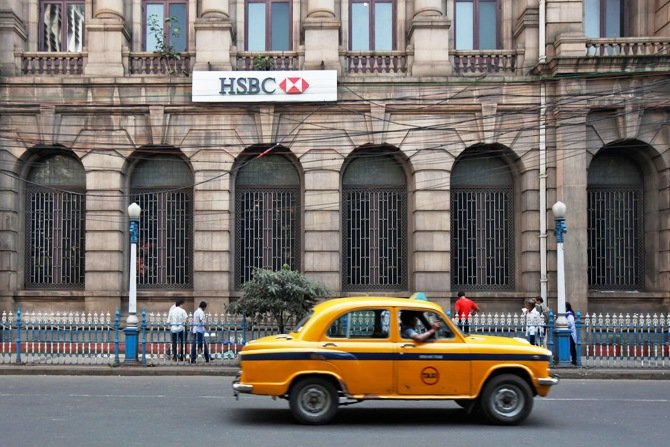 A yellow ambassador taxi drives past the HSBC bank building in Kolkata.