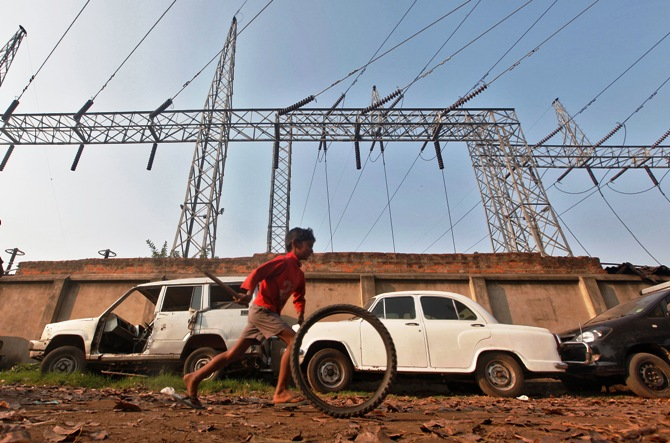 A boy plays with a tyre in front of electric pylons installed at a power house in Kolkata.