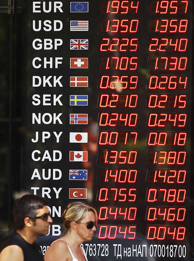 People walk past a display board of a currency exchange office in Sofia, Bulgaria.