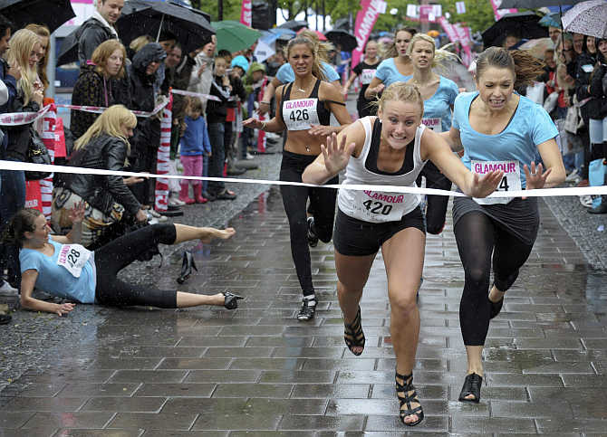 Elin Bjerre of Kristianstad in southern Sweden crosses the finish line first to win the 100m final of the Stiletto Run in Stockholm, Sweden.