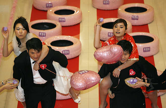 Couples go through an obstacle course during a wife-carrying competition at a shopping mall in Hong Kong.