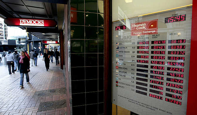 Foreign exchange rates are on display at a Thomas Cook shop in Lambton Quay in Wellington, New Zealand.