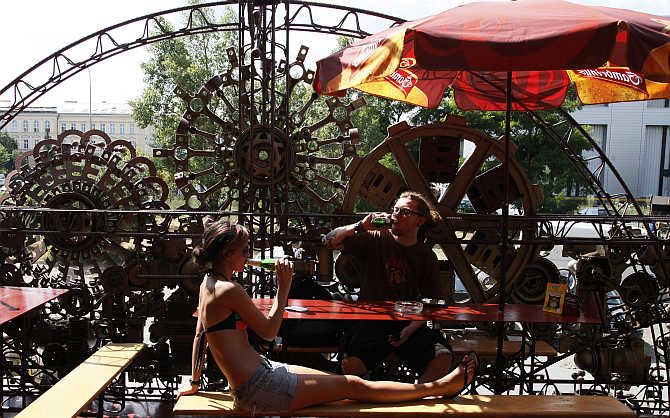 Customers enjoy drinks at a cafe bar in Prague's district of Holesovice, Czech Republic.