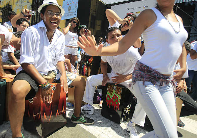 Participants dance and play their cajons, a popular Peruvian instrument, during the International Festival of the Peruvian Cajon in Lima's Plaza Mayor.