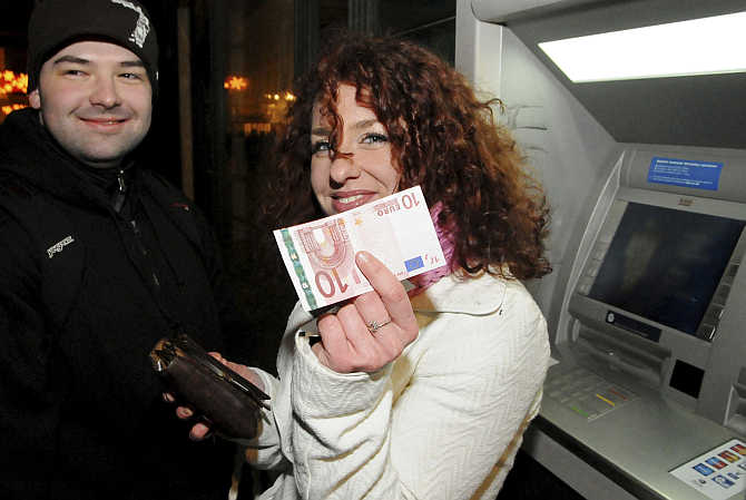 A woman holds up a euro note in Bratislava, Slovakia.