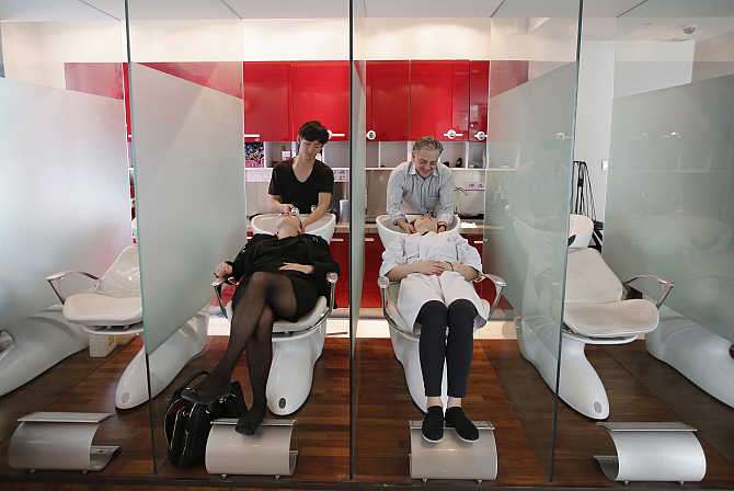 French hair dresser Eric Constantino, right, washes his staff's hair during a demonstration at his shop in Beijing, China.