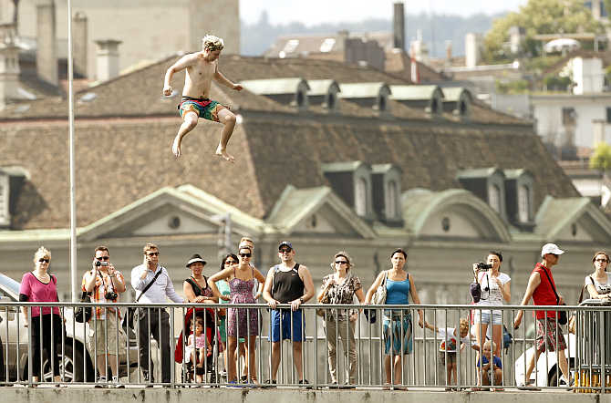 People standing on the Quaibruecke bridge watch a man jump from a 10-metre-high public diving platform into Lake Zurich in Zurich, Switzerland.