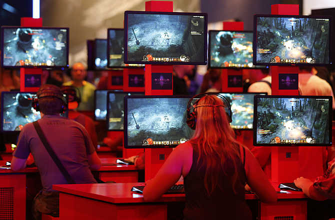 Visitors play Diablo video game at the Blizzard exhibition stand during the Gamescom 2013 fair in Cologne, Germany.