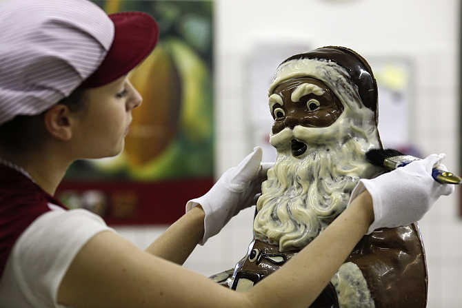 A confectioner makes final touches to a 90 centimetre high handmade chocolate Santa Claus figure, in the workshop of the Felicitas chocolate shop, in Hornow, south of Berlin, Germany.