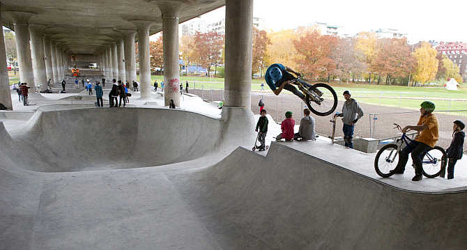 Children try out a skateboard park built under a concrete viaduct in Ralambshov Park in central Stockholm, Sweden.