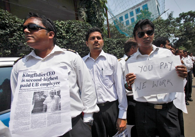 Employees of Kingfisher Airlines hold posters during a protest against the company near the domestic airport in Mumbai.