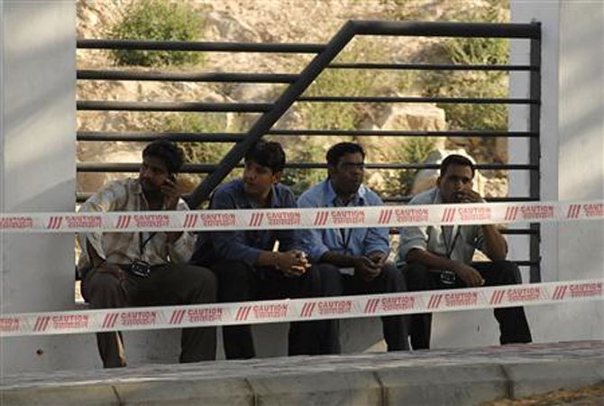 A file photo of employees sitting outside the head office of Satyam Computer Services during a smoking break