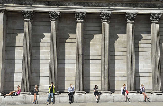 Workers relax during the lunch hour outside the Bank of England in the City of London.