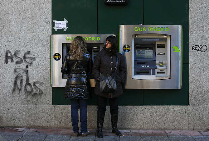 Women use an ATM at a Caja Madrid-Bankia branch in Madrid, Spain.